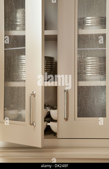 Dishes stacked in open kitchen cupboard - Stock Image