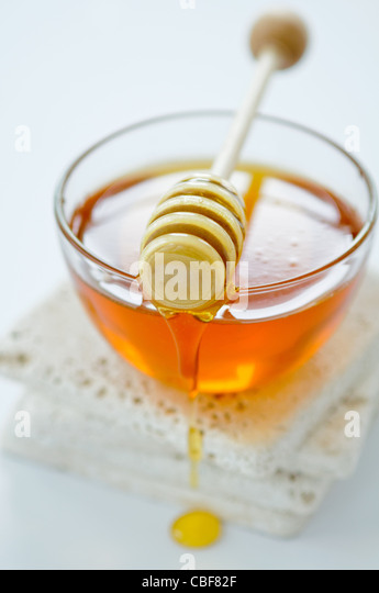 Bowl of runny honey with honey dipper - Stock Image