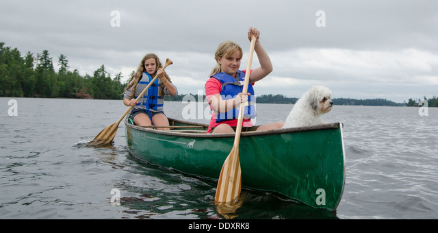 Two girls rowing a boat in a lake, Lake of The Woods, Ontario, Canada - Stock Image