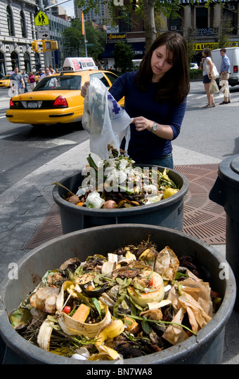 Union Square, NYC, 2009 - Young woman emptying a bag of food waste into compost heaps at an outdoor farmer's - Stock Image