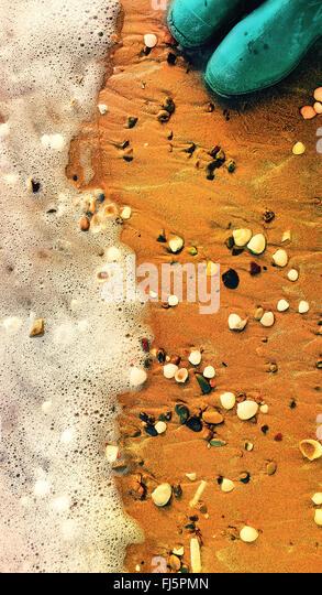 wellingtons on the pebble beach - Stock Image