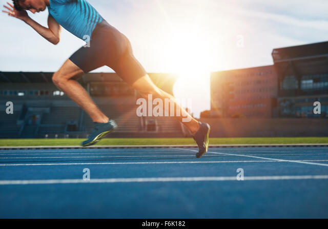 Shot of young male athlete launching off the start line in a race. Runner running on racetrack in athletics stadium. - Stock Image