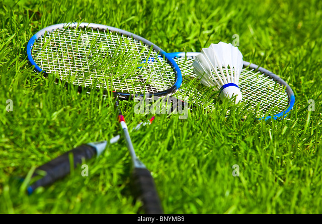 Badminton rackets on green grass. - Stock Image