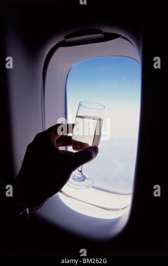 Glass of champagne at 30000 feet and aircraft window - Stock Image