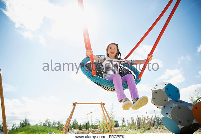 Carefree girl swinging at sunny playground - Stock Image