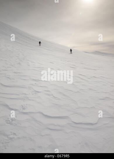 a heavily textured mountain snowfield with two men on snowshoes in the distance - Stock Image