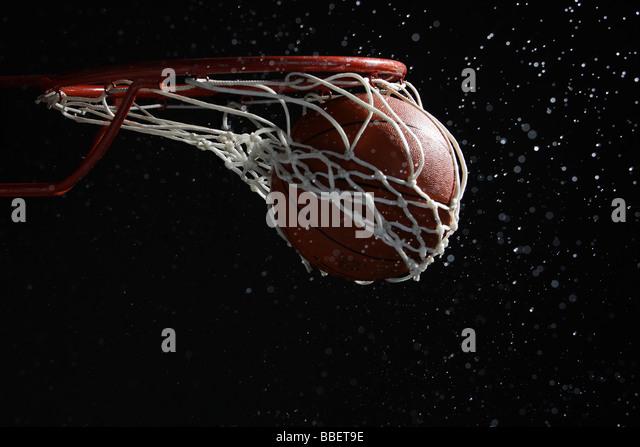 Basketball going through hoop - Stock Image