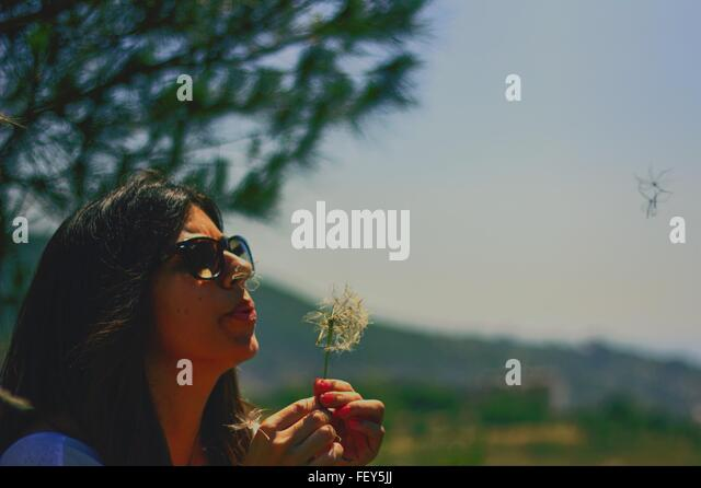 Young Woman Blowing Dandelion Seed While Standing In Park - Stock Image