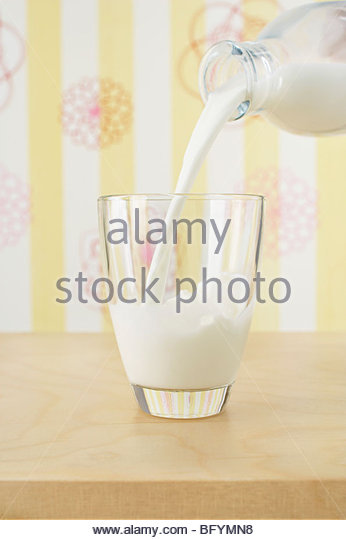 milk being poured into glass - Stock Image