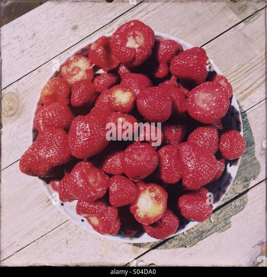 A bowl of strawberries is seen. - Stock Image