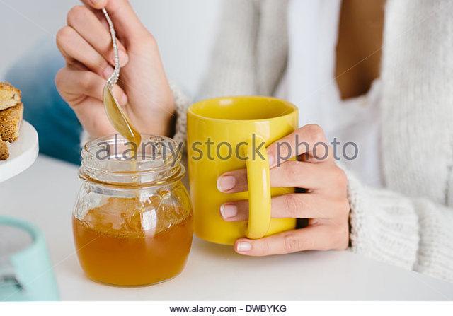 Young woman having honey drink - Stock-Bilder