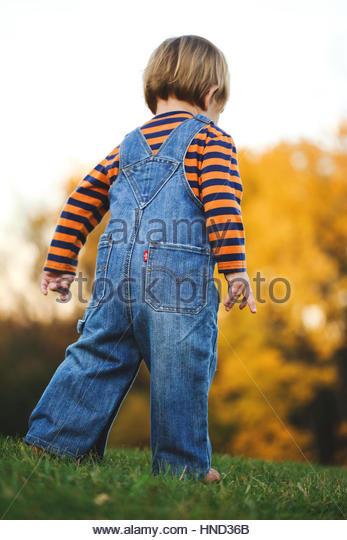 Toddler boy walking away - Stock Image