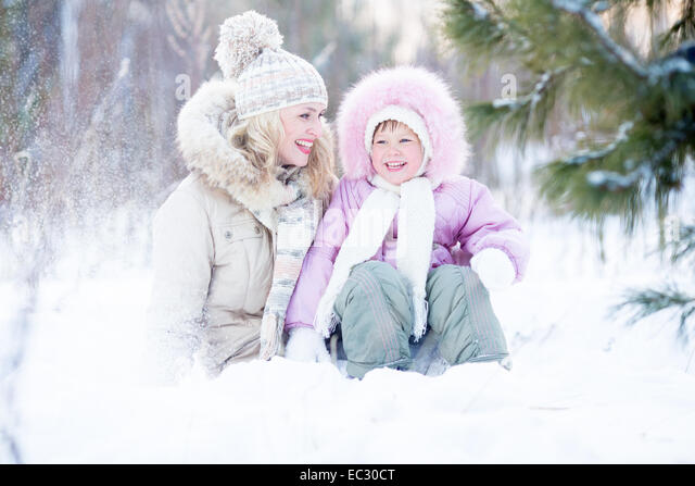 Happy family sitting in snow outdoor wintertime - Stock-Bilder