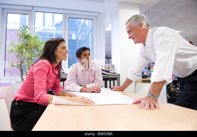 Team discussion over plans in an architects office. - Stock-Bilder