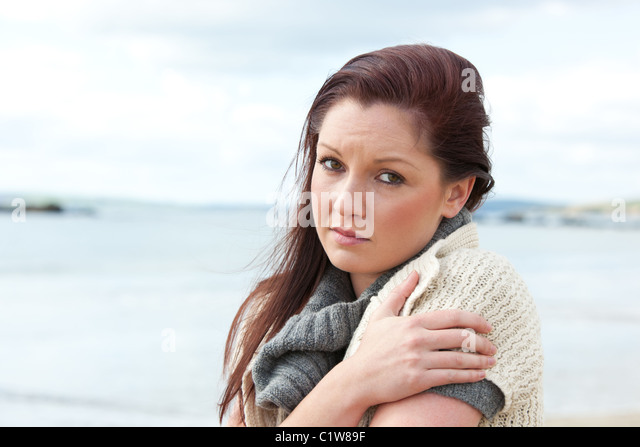 Downcast woman wearing hat and scarf on the beach - Stock Image