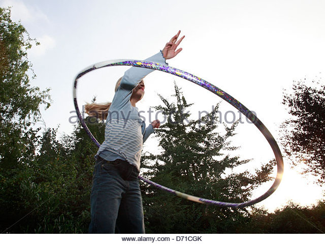 Low angle view of a girl playing with a hula hoop - Stock-Bilder