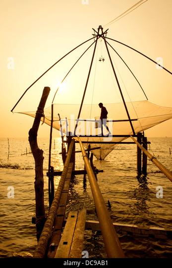Fisherman holding a landing net in a Chinese fishing net at sunrise - Stock-Bilder