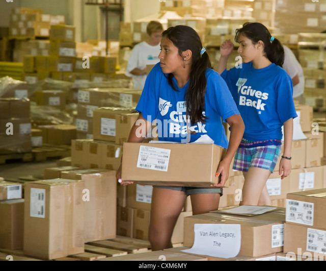 Volunteers Sort and Pack Free Books for Low-Income Children - Stock Image