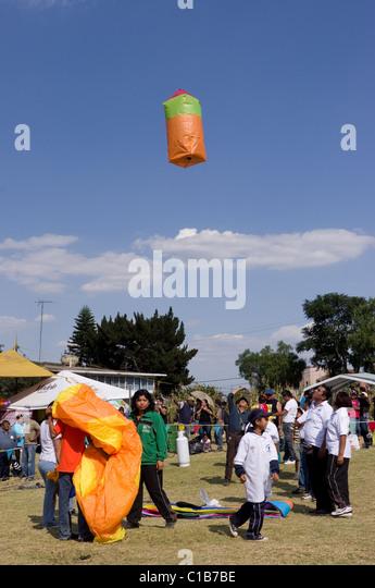 Orange Globo de Cantolla (hot air paper balloon) elevating in San Agustin Ohtenco, Mexico - Stock Image