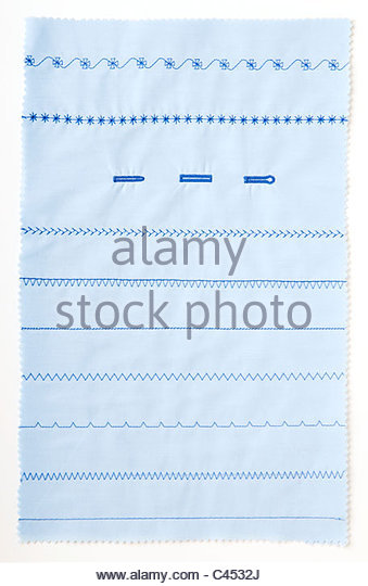 Selection of machine stitching on pale blue fabric, close-up - Stock Image