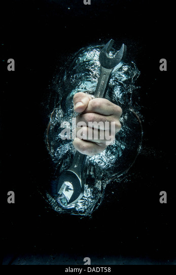 Male hand gripping wrench beneath water - Stock Image