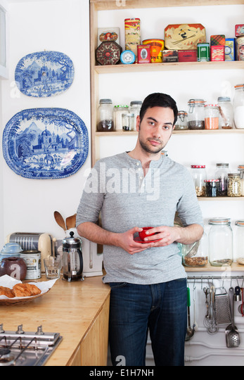Mid adult man standing in kitchen holding coffee cup - Stock Image