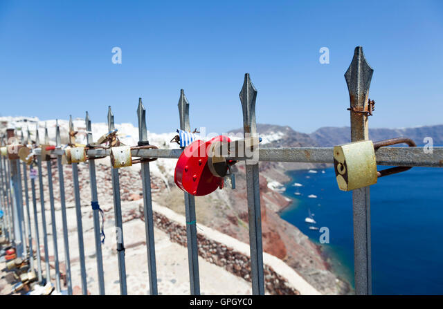 Multi-coloured lover's padlocks adorn a set of railings in the town of Oia, on the beautiful and romantic Greek - Stock Image
