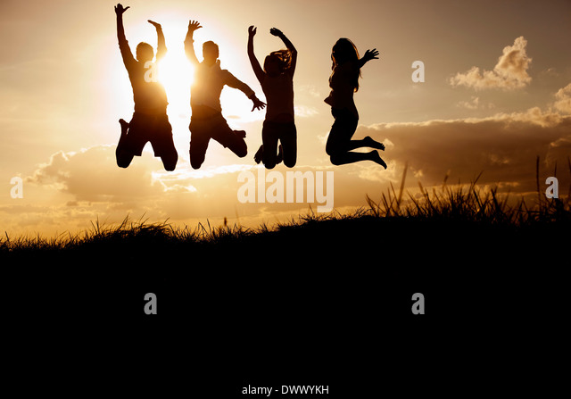 Silhouetted image of friends jumping on beach against sky - Stock Image