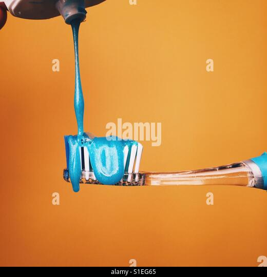 Tooth paste being put on a toothbrush against a yellow background. - Stock-Bilder
