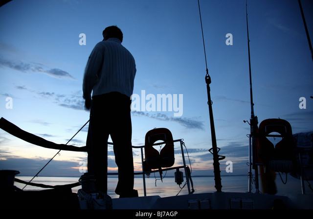 Man angling on a sailing boat - Stock Image