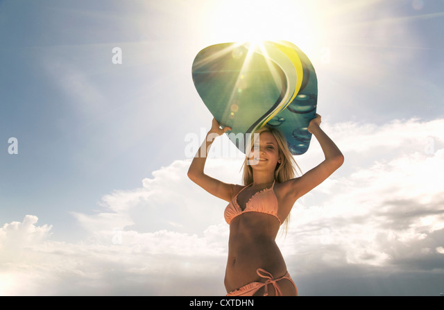 Woman carrying boogie board outdoors - Stock Image