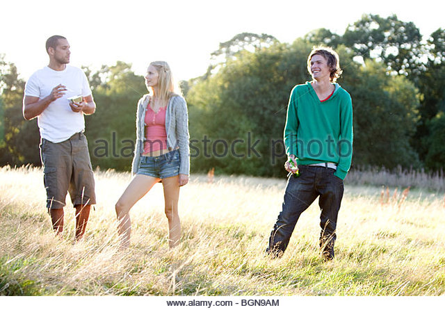 Three young friends standing in a field, one eating - Stock Image