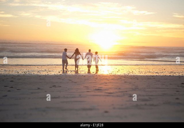 Family holding hands on beach, Cape Town, South Africa - Stock Image