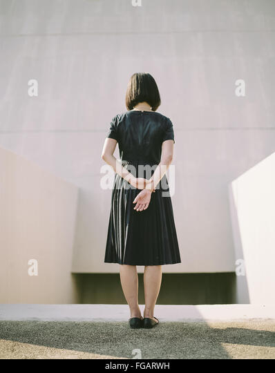 Rear View Of Woman With Hands Behind Back Standing Against Wall - Stock Image