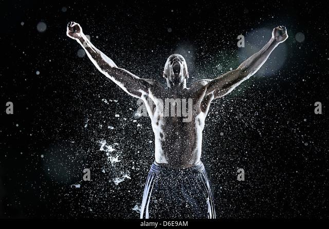 African American athlete splashing in water - Stock Image