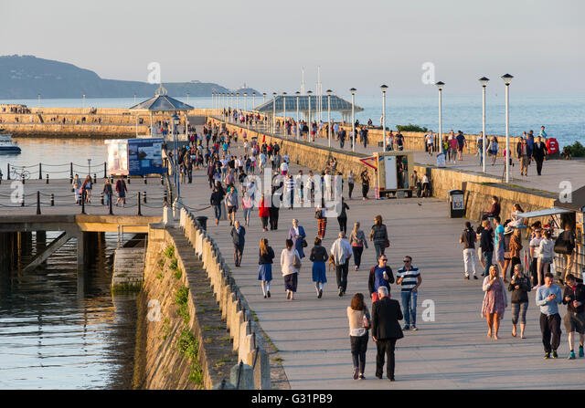 large crowd people walking dun laoghaire pier walk - Stock Image