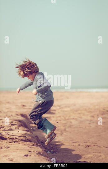 Boy jumping in the sand on the beach, Morocco - Stock Image