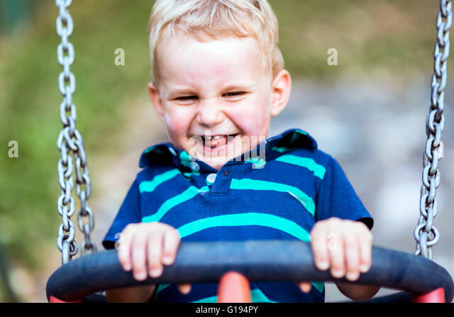 Playful child on swing outdoors smiling sincerely - Stock Image
