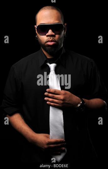 Portrait of young African American man wearing sunglasses and white tie - Stock-Bilder