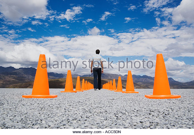 Man standing in-between two rows of safety cones - Stock Image