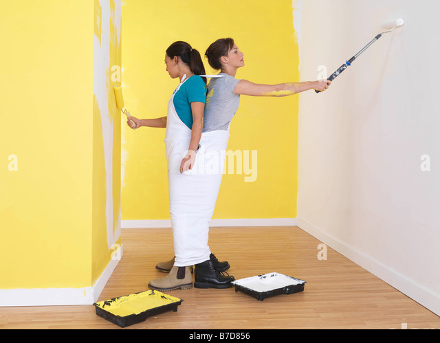 Girls painting in the same trousers. - Stock Image