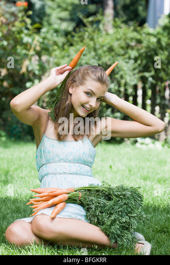 young woman with fresh carrots - Stock Image