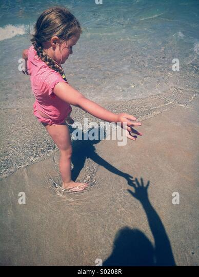 Little girl touching a shadow - Stock Image