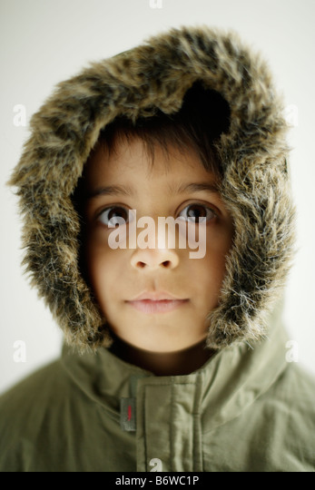 Child wears Parka coat with hood zipped up Boy aged six years - Stock Image