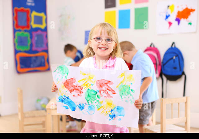 Preschool girl holding up artwork - Stock Image