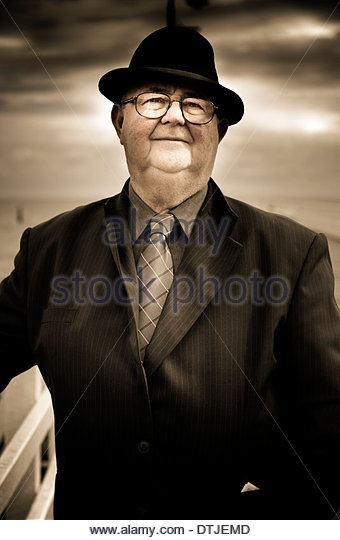 Old Person Standing By A Railing At A Beach Location Wearing Business Suit And Tie Thinking, Recalling And Recollecting - Stock Image