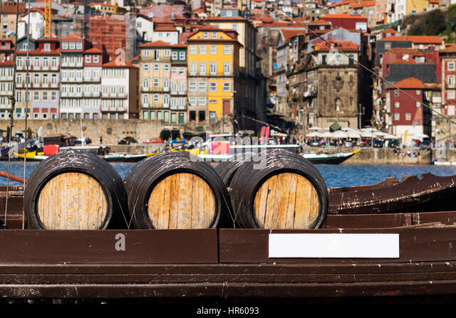 Detail of Port Wine barrels in a boat in the Douro River with the city of Porto in the background - Stock-Bilder