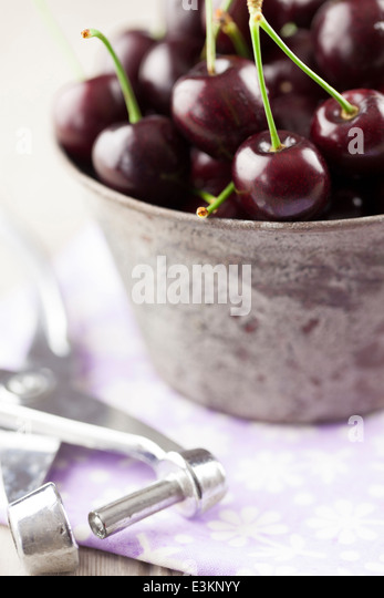 English Cherries in Metal Bowl with Cherry Stoner - Stock Image