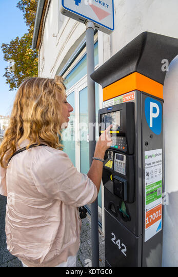 Woman paying for car parking at ticket machine, La Rochelle, France. - Stock Image