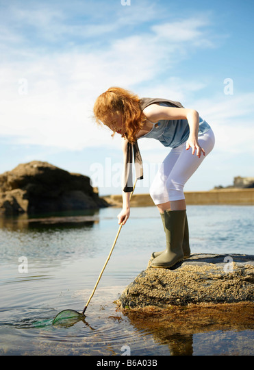 Young girl fishing in rock pool - Stock-Bilder